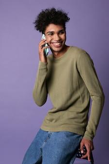 Portret van jonge brunette man zit mobiel in de hand op paarse achtergrond