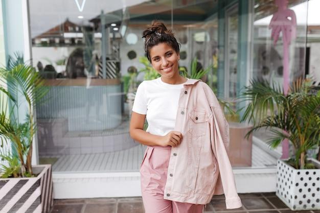 Portret van jonge brunette vrouw in wit t-shirt en denim roze jasje poseren met glimlach naast schattige bar