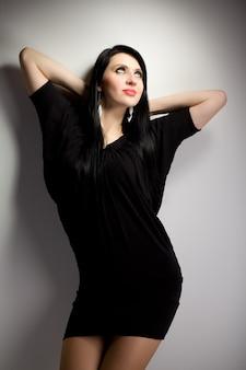 Portret van jonge brunette vrouw in zwarte jurk permanent op witte achtergrond in fotostudio en naar beneden te kijken