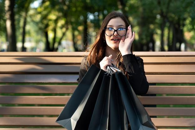 Portret van jonge brunette vrouw met boodschappentassen op bankje in park.