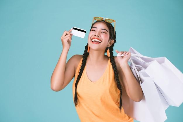 Portret van jonge brunette vrouw met creditcard en boodschappentassen