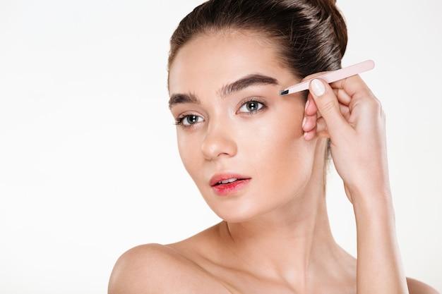 Portret van jonge brunette vrouw met zachte huid wenkbrauwen epileren met een pincet