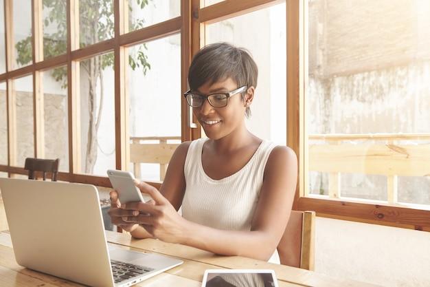 Portret van jonge brunette vrouw zitten in café met laptop