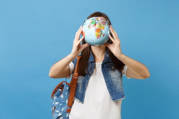 Portret van jonge casual brunette vrouw student met rugzak houden en bedekken gezicht met wereldbol met bril geïsoleerd op blauwe achtergrond. onderwijs in het concept van de middelbare schooluniversiteit.