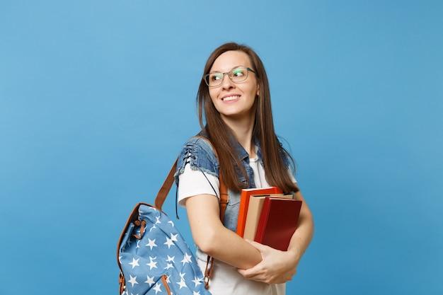 Portret van jonge casual mooie vrouw student in glazen met rugzak opzij kijken op kopie ruimte schoolboek geïsoleerd op blauwe achtergrond te houden. onderwijs in het concept van de middelbare schooluniversiteit.