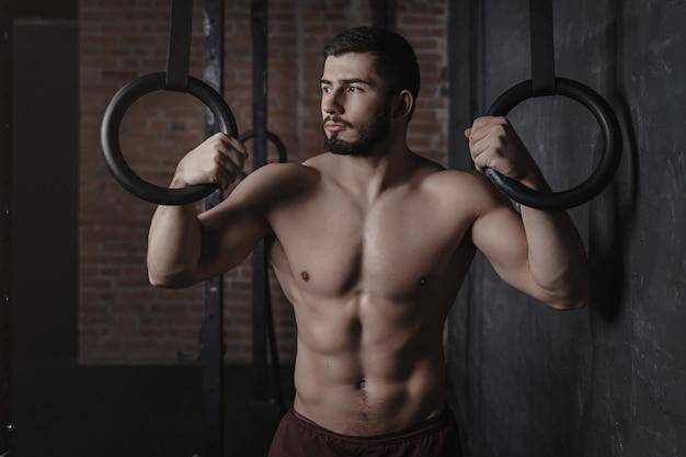 Portret van jonge crossfit atleet gymnastische ringen houden in de sportschool.
