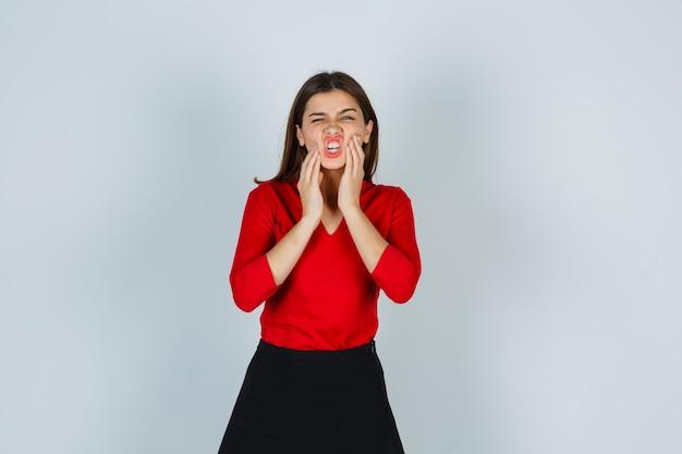 Portret van jonge dame hand in hand op wangen in rode blouse