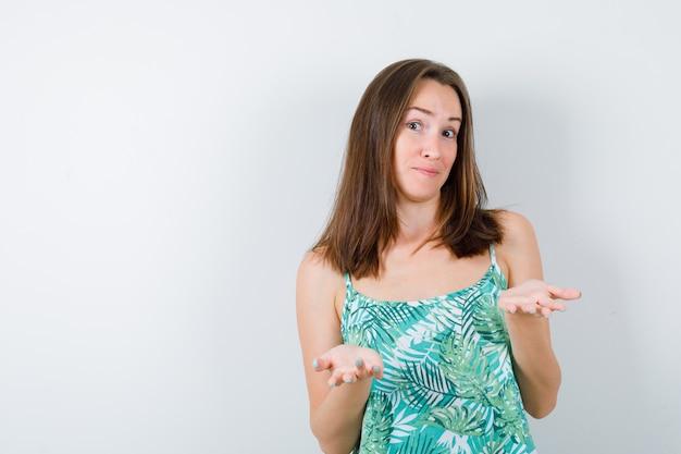 Portret van jonge dame spreidt handpalmen in een onwetend gebaar in blouse en kijkt hulpeloos vooraanzicht