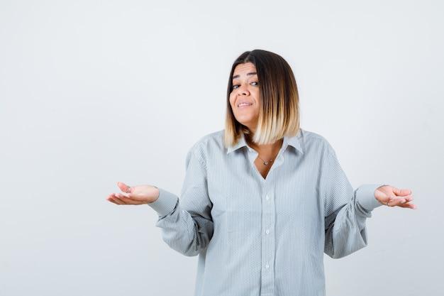 Portret van jonge dame spreidt handpalmen opzij in oversized shir vooraanzicht