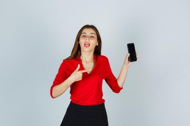 Portret van jonge dame wijzend op mobiele telefoon in rode blouse