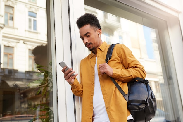 Portret van jonge denkende donkere man in geel shirt op straat lopen, telefoon vasthoudt, chatten met vriendin, ziet er concentraat uit.