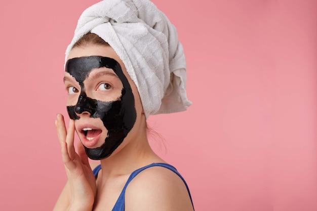 Portret van jonge denkende vrouw na douche met een handdoek op haar hoofd, met zwart masker, raakt gezicht, staat.