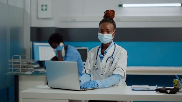 Portret van jonge dokter die laptoptechnologie op bureau gebruikt