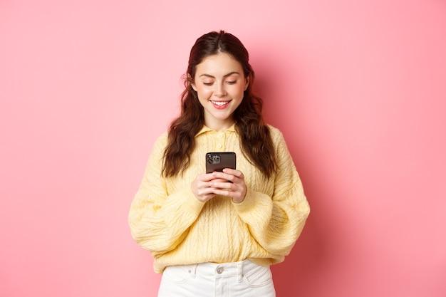 Portret van jonge donkerbruine vrouw die het smartphonescherm leest en glimlacht chatten op sociale media app die online staand tegen roze muur winkelt
