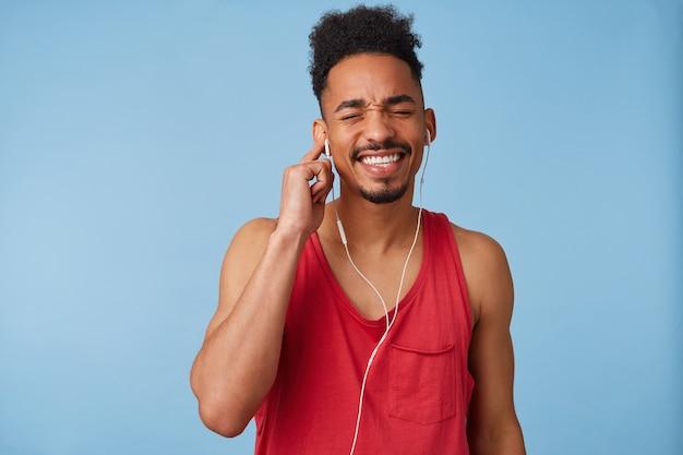 Portret van jonge donkere aantrekkelijke kerel in een rood t-shirt, sluit zijn ogen en zingt luid een favoriet lied dat in hoofdtelefoons wordt afgespeeld, houdt oortje vast met rechterhandstandaards.