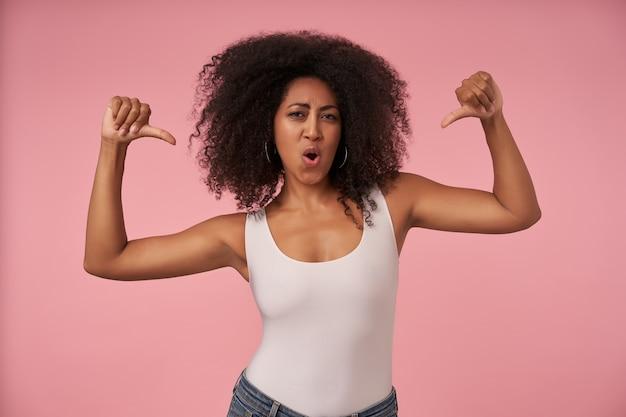 Portret van jonge donkere dame in vrijetijdskleding zelfverzekerd, poseren op roze met opgeheven duimen naar beneden