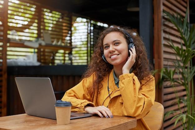 Portret van jonge donkere krullend student meisje luistert naar muziek en droomt van weekendfeest, zittend op een caféterras, gekleed in een gele jas, koffie drinken, werkt op een laptop.