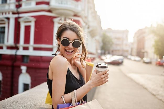 Portret van jonge donkerharige blanke vrouw in zonnebril en zwarte jurk lachen