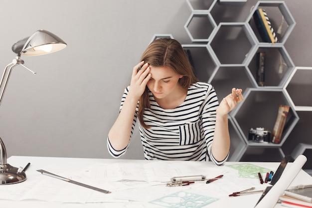 Portret van jonge donkerharige knappe vrouwelijke freelance ontwerper in gestreept casual shirt handen uitspreiden, gefrustreerd, grote fout opmerken in financiële berekeningen
