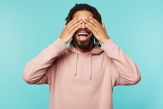 Portret van jonge donkerhuidige brunette bebaarde man die gelukkig lacht terwijl hij opgeheven handpalmen op zijn ogen houdt, gekleed in roze hoodie terwijl hij over blauwe achtergrond staat