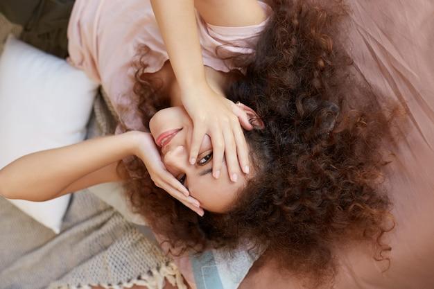 Portret van jonge donkerhuidige dame geniet van de zonnige dag thuis en lachend, brengt ze vrije dag thuis door, tegens gezicht met handen en liggend op het bed.