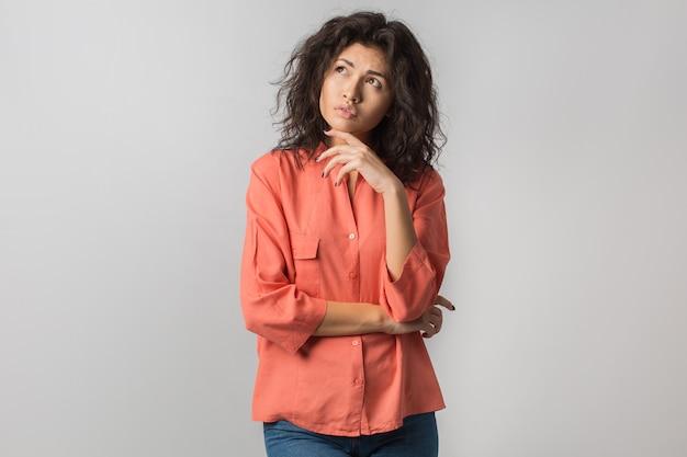 Portret van jonge doordachte brunette vrouw in oranje shirt, krullend haar, zomerstijl, gefrustreerde gezichtsuitdrukking, opzoeken, denken, probleem, idee, gemengd ras, geïsoleerd