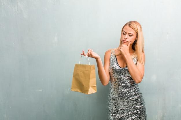 Portret van jonge elegante blonde vrouw die denkt en omhoog kijkt, verward over een idee, zou een oplossing proberen te vinden. winkelmand houden.