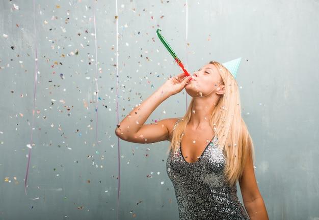 Portret van jonge elegante blonde vrouw die een partij viert.