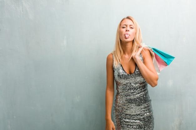 Portret van jonge elegante blonde vrouw uitdrukking van vertrouwen en emotie. winkelmand houden.