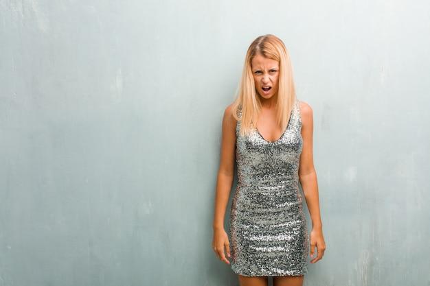 Portret van jonge elegante blondevrouw zeer boos en verstoord, zeer gespannen