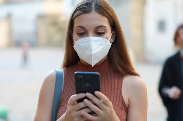 Portret van jonge elegante vrouw die kn95 ffp2-maskerberichten met mobiele telefoon in stadsstraat dragen