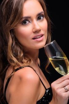 Portret van jonge elegante vrouw het drinken champagne tegen zwarte