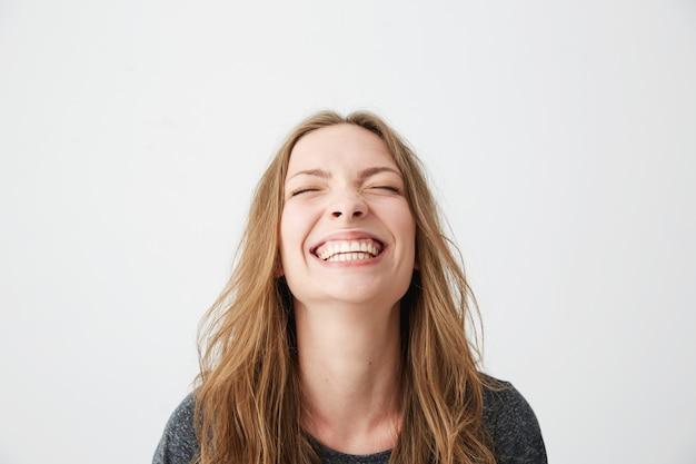 Portret van jonge emotionele mooi meisje lachen met gesloten ogen.