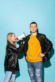 Portret van jonge emotionele vrouw die met megafoon tegen zijn vriend schreeuwt
