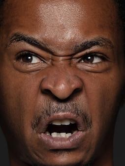 Portret van jonge en emotionele afro-amerikaanse man close-up. zeer gedetailleerde fotoshoot van mannelijk model met verzorgde huid en heldere gezichtsuitdrukking. concept van menselijke emoties. boos, agressief.
