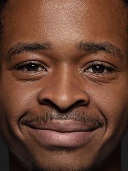 Portret van jonge en emotionele afro-amerikaanse man close-up. zeer gedetailleerde fotoshoot van mannelijk model met verzorgde huid en heldere gezichtsuitdrukking. concept van menselijke emoties. kijkend naar de camera.