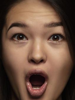 Portret van jonge en emotionele chinese vrouw close-up. zeer gedetailleerde fotoshoot van een vrouwelijk model met een verzorgde huid en een heldere gezichtsuitdrukking. concept van menselijke emoties. benieuwd, verbaasd.