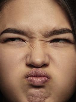 Portret van jonge en emotionele chinese vrouw close-up. zeer gedetailleerde fotoshoot van een vrouwelijk model met een verzorgde huid en een heldere gezichtsuitdrukking. concept van menselijke emoties. walging.