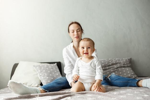 Portret van jonge en gelukkige familie van knappe moeder en pasgeboren zoon kostbare tijd samen doorbrengen, glimlachend en spelen in de slaapkamer.