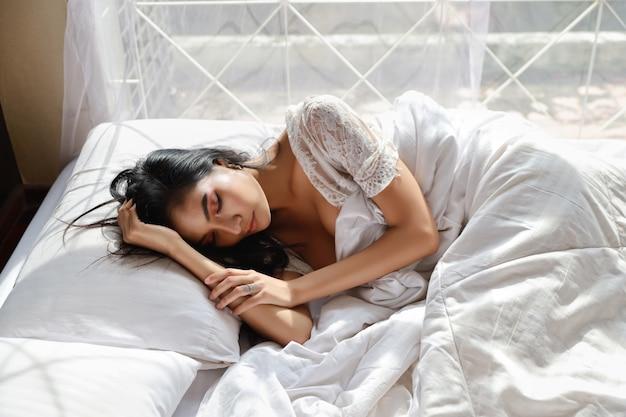 Portret van jonge en mooie aziatische vrouw die de witte slaap van de lingerienachtkleding in slaapkamer dragen. jonge schattige vrouw lang haar liggend op bed en laat wakker. lifestyle concept