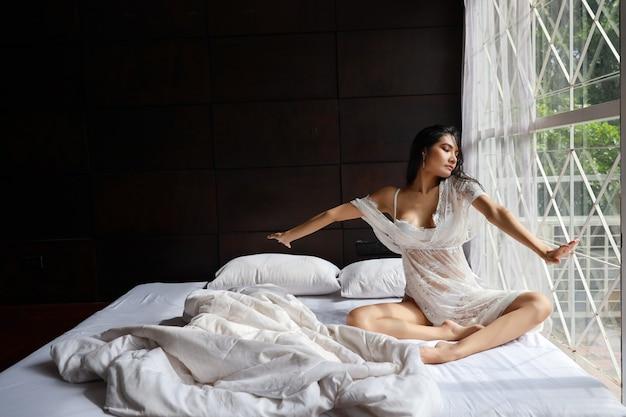 Portret van jonge en mooie aziatische vrouw die het witte lingerienachtkleding uitrekken zich in slaapkamer dragen. jonge schattige vrouw lang haar zittend op bed en laat wakker. lifestyle concept