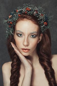 Portret van jonge en mooie vrouw met krans op haar hoofd close-up