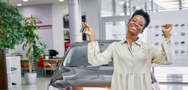 Portret van jonge en mooie zwarte vrouw met sleutels van haar nieuwe auto