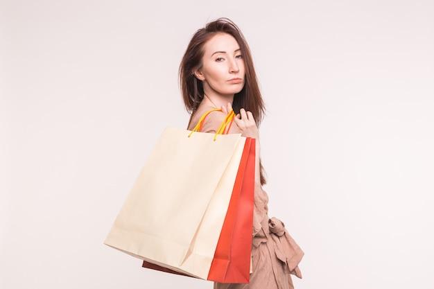 Portret van jonge ernstige aziatische vrouw met boodschappentassen op witte achtergrond