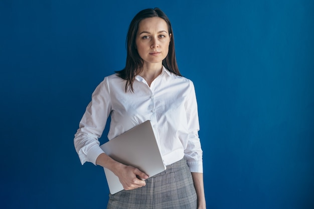 Portret van jonge ernstige bedrijfsvrouw die met laptop camera bekijkt.