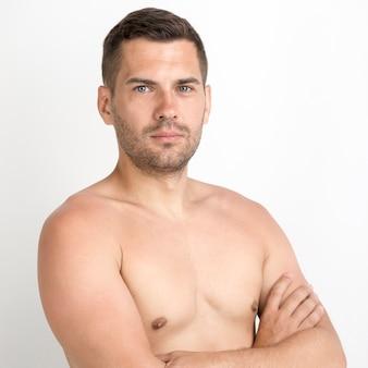 Portret van jonge ernstige man met gekruiste arm tegen witte achtergrond
