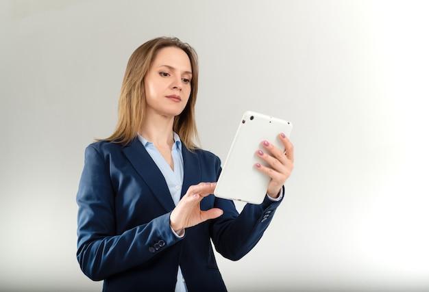 Portret van jonge ernstige vrouw die iets op haar witte tablet leest dat op grijs wordt geïsoleerd