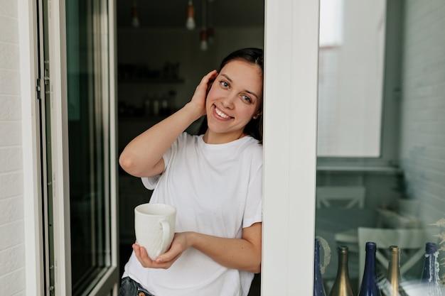 Portret van jonge europese vrouw met donker haar en een gezonde huid lachend met koffie in de ochtend in de moderne lichte keuken.