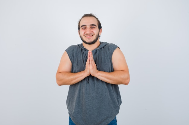 Portret van jonge fit mannelijke hand in hand biddend gebaar in mouwloze hoodie en op zoek naar hoopvol vooraanzicht
