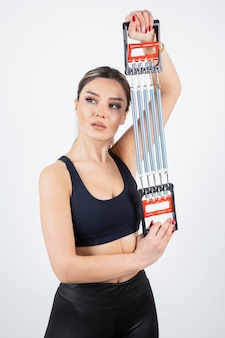 Portret van jonge fit vrouw training met gym tool.
